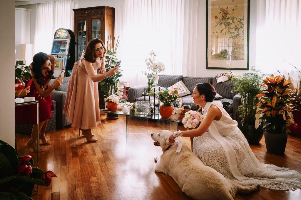 la sposa è pronta per uscire di casa la mamma e la sorella la fotografano con i propri cellulari vicino al loro cane