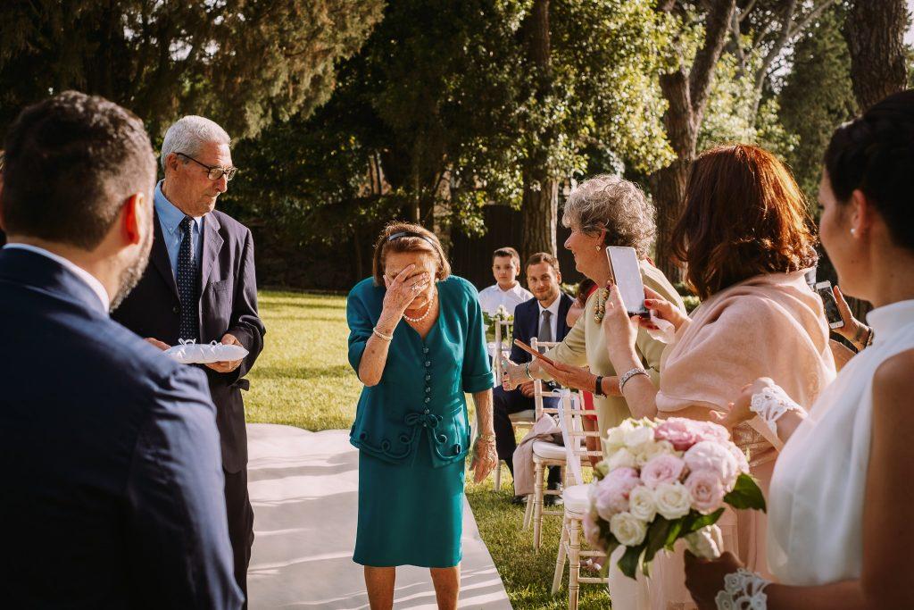 i nonni degli sposi percorrono il corridoio della cerimonia di matrimonio al borgo della merluzza per portare le fedi agli sposi e la nonna della sposa si commuove
