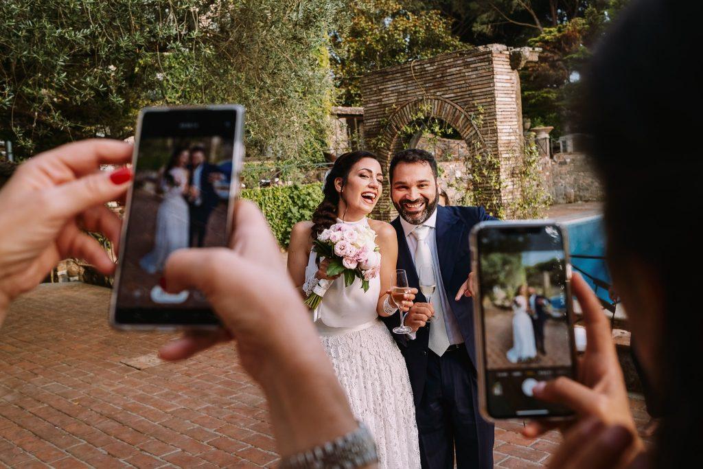 gli sposi felici e sorridenti posano per le foto degli amici