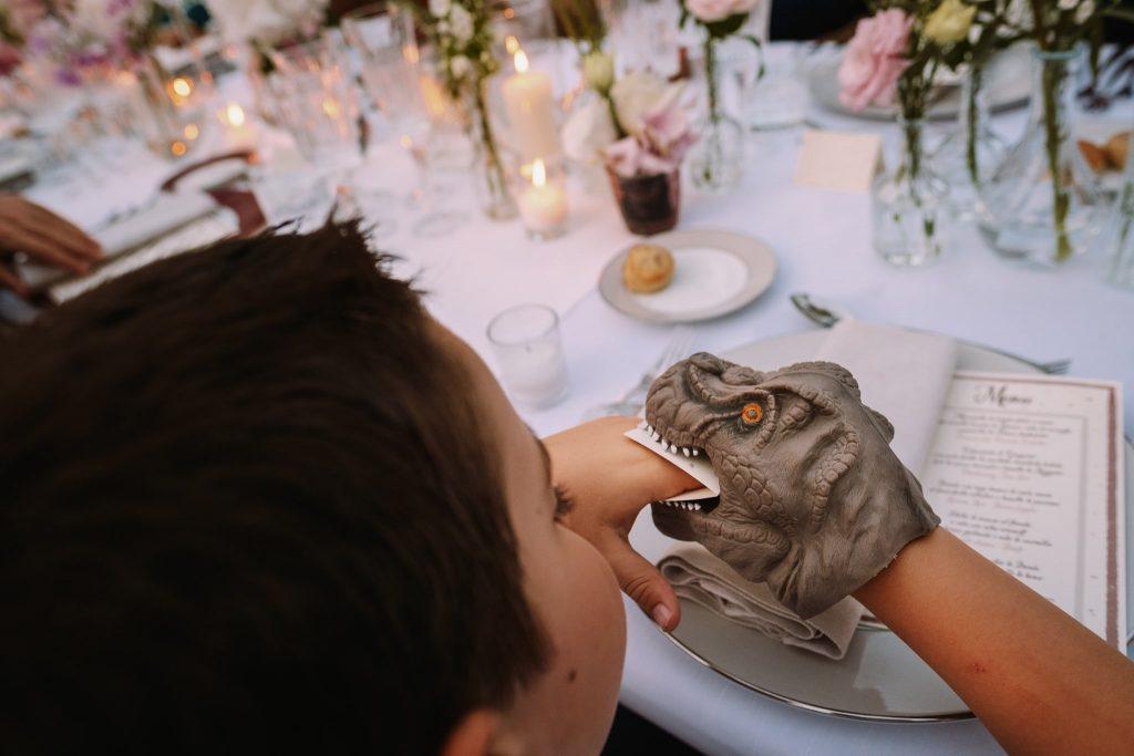 un bambino gioca con un pupazzo a forma di dinosuaro durante la cena di matrimonio al borgo della merluzza