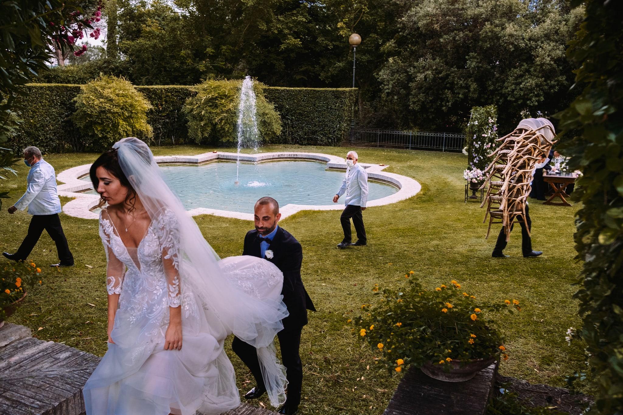 sposi-si-allontanano-dopo-cerimonia-di-matrimonio-sul-prato-di-villa-dei-quintili-a-roma-sulla-appia-antica-mentre-camerieri-tolgono-le-sedie-e-preparano-aperitivo