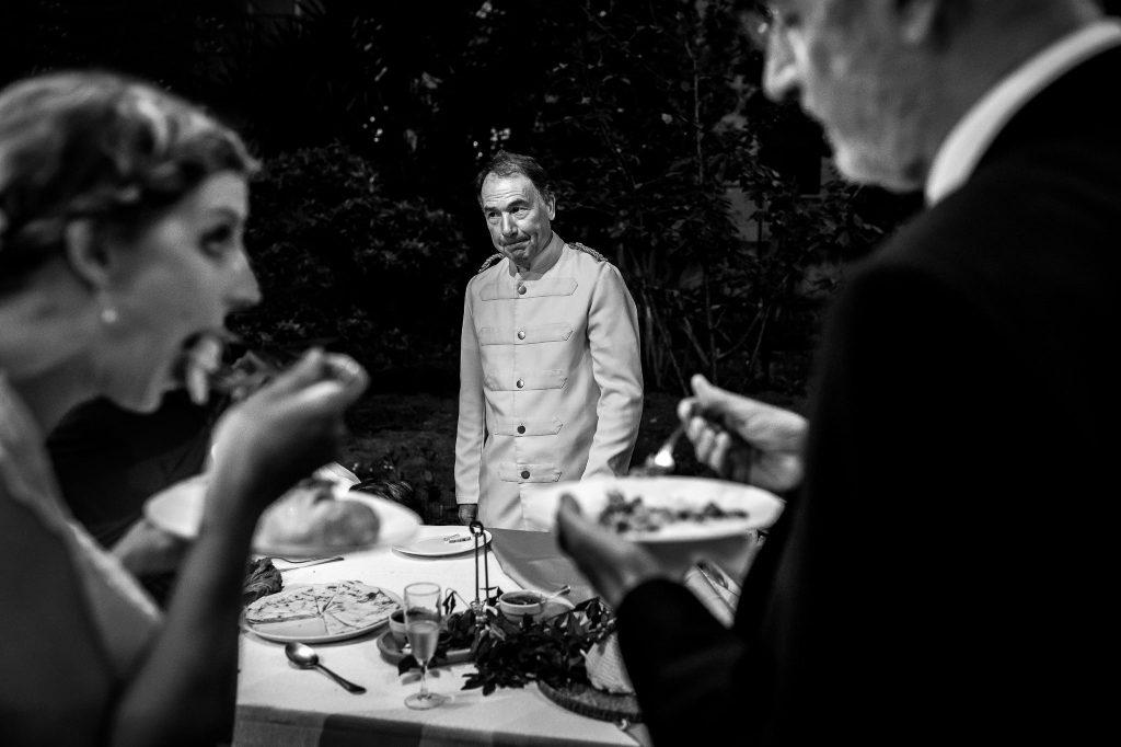 cameriere-divertito-serve-a-buffet-di-matrimonio-mentre-invitati-mangiano-pietanze-ad-un-matrimonio-durante-apertitivo