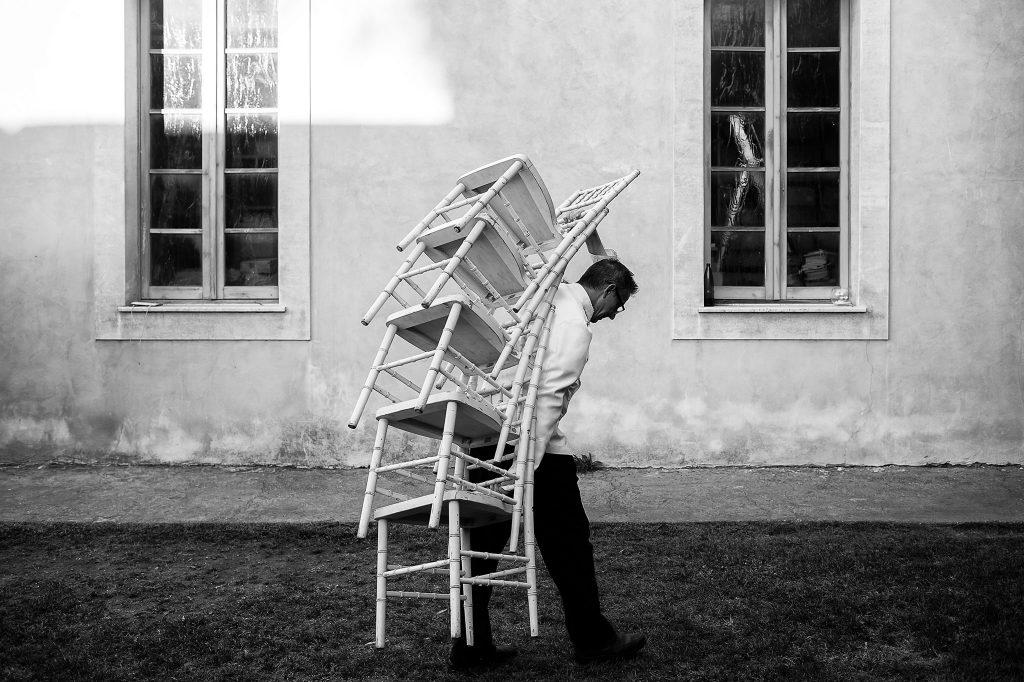 cameriere-sposta-sedie-durante-un-matrimonio-con-lo-sfondo-della-villa-per-matrimoni-a-roma