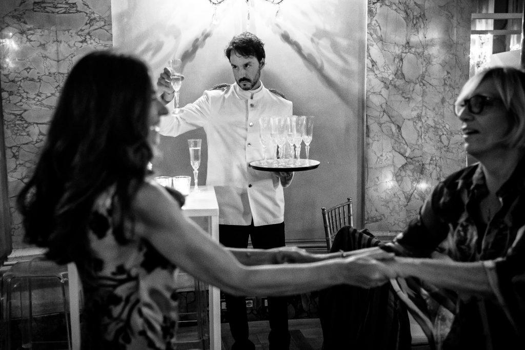cameriere-controlla-bicchieri-durante-aperitivo-di-matrimonio-mentre-invitati-a-matrimonio-ballano