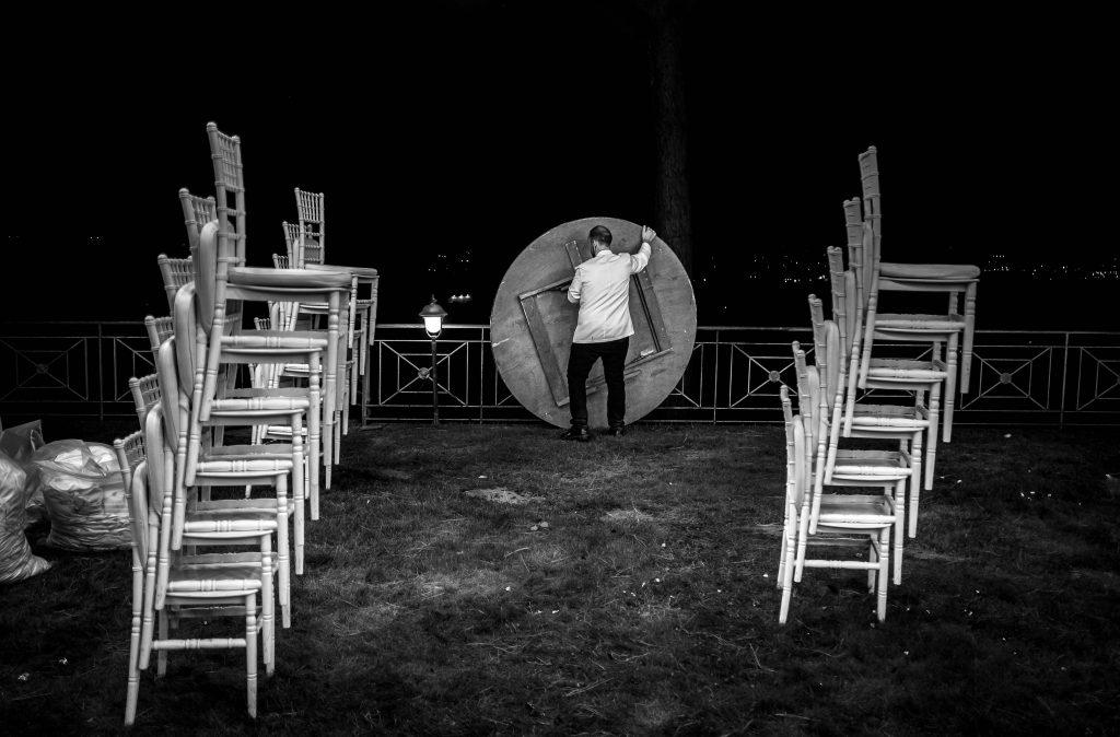 cameriere-sposta-un-tavolo-durante-un-matrimonio-con-in-primo-piano-sedie-del-ricevimento-di-matrimonio
