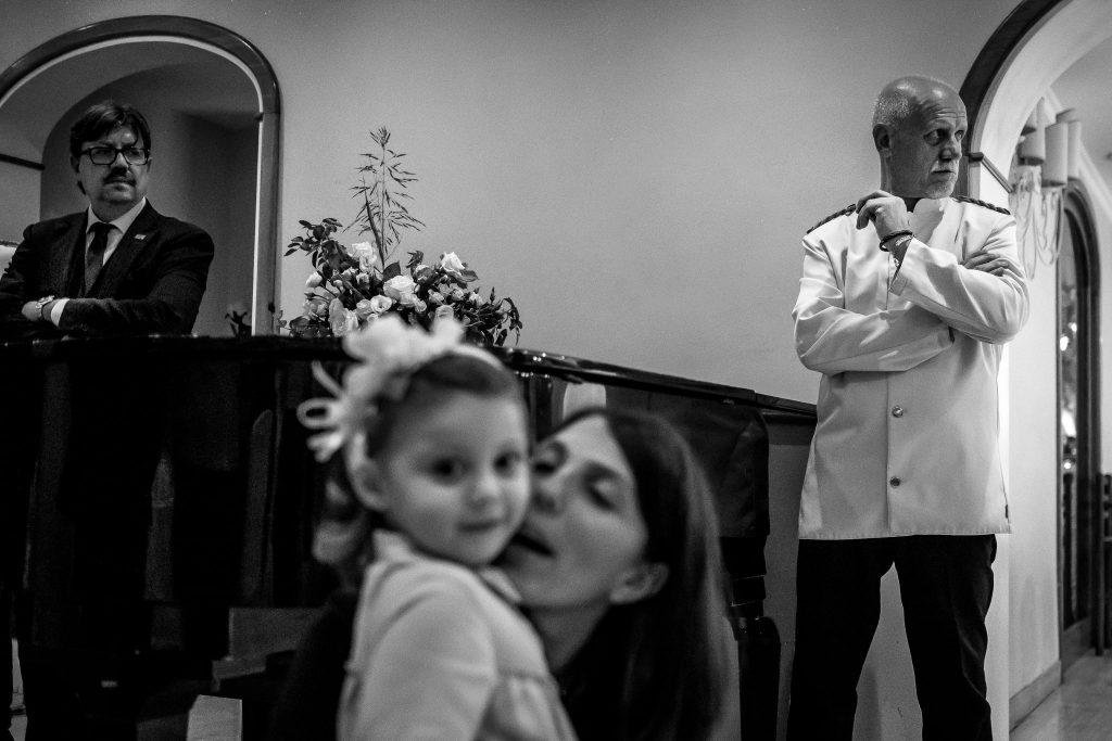cameriere-e-metre-controllano-la-sala-del-ricevimento-di-un-matrimonio-mentre-mamma-con-bambino-giocano-a-villa-il-sogno-a-roma