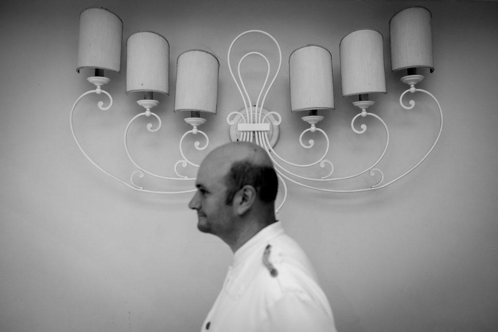 cameriere-passa-di-fronte-una-lampada-da-muro-nella-sala-del-ricevimento-di-un-matrimonio-a-roma