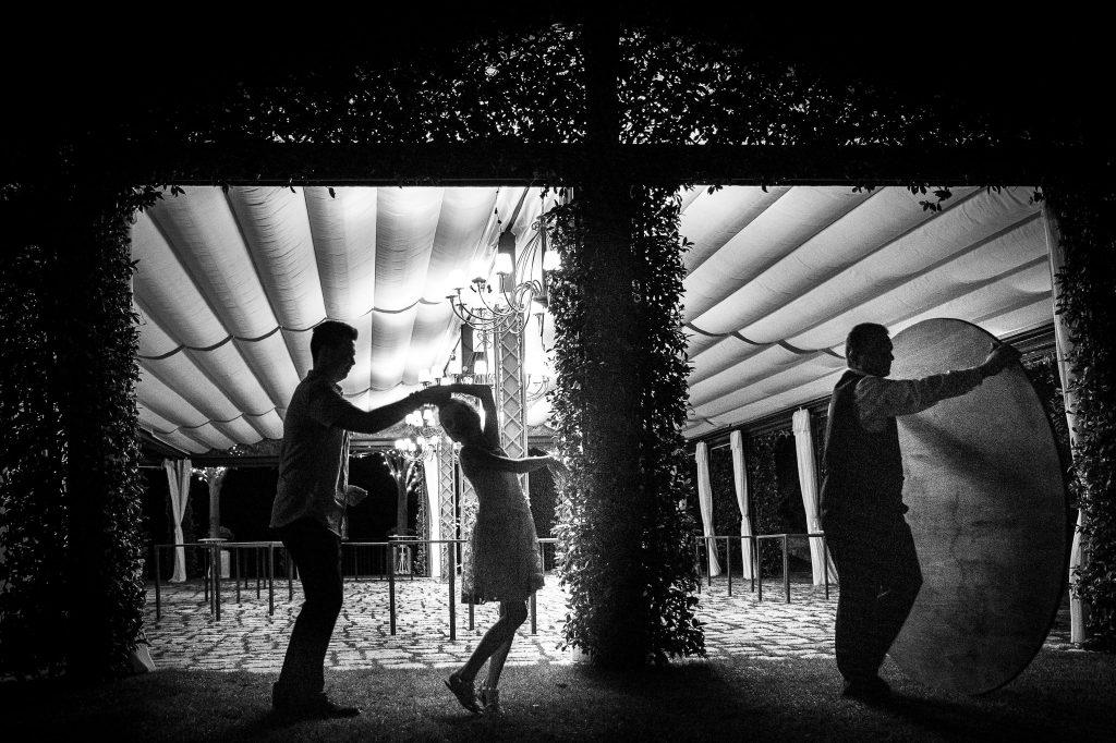 sposi-ballano-alla-fine-del-matrimonio-mentre-cameriere-porta-via-un-tavolo-dalla-sala-del-ricevimento-sottto-uno-tensostruttura