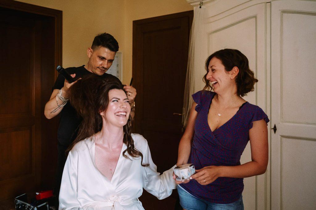 la sposa ride con l'amica durante i preparativi del matrimonio a san gimignano