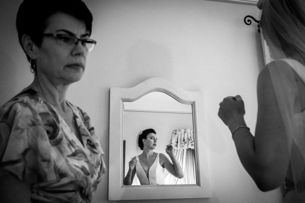 la sposa indossato l'abito si guarda allo specchio con vicino la mamma prima di uscire per andare alla cerimonia di matrimonio a san gimignano