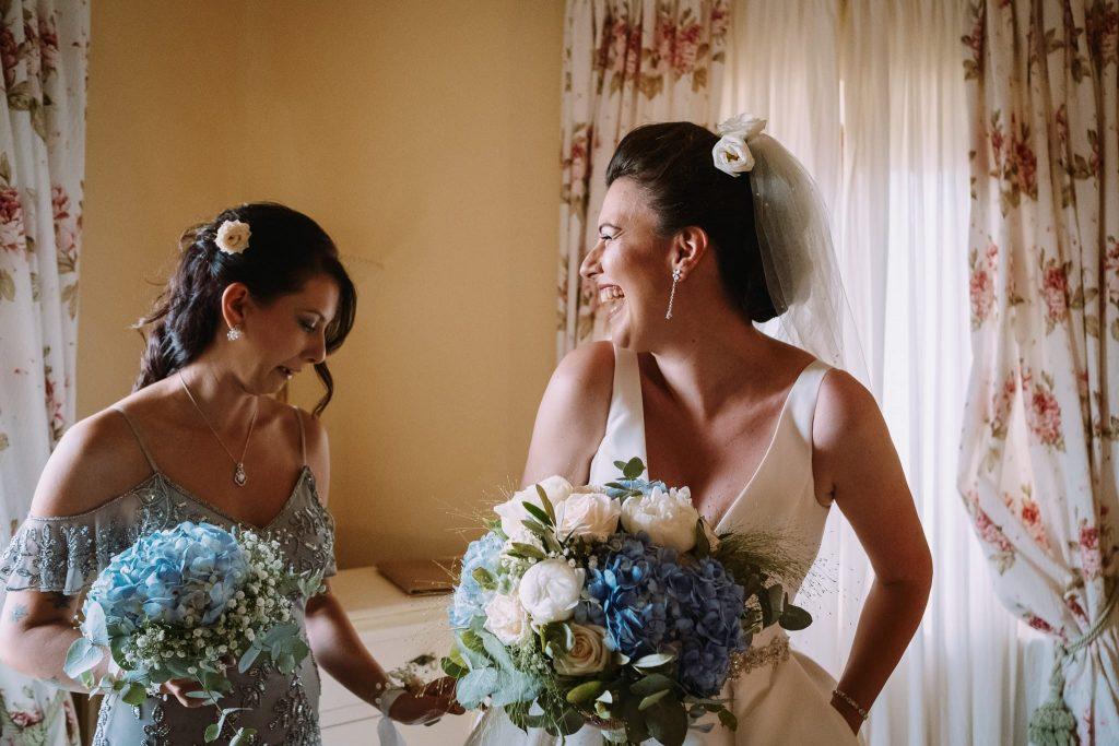 la sposa con il bouquet di fiori ride con la testimone alla fine della preparazione