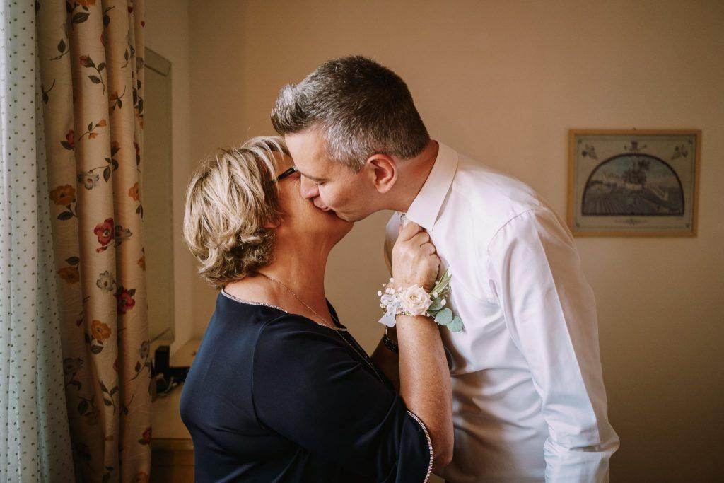 lo sposo e la mamma dello sposo si danno un bacio prima del matrimonio a san gimignano