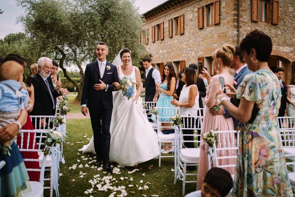 lo sposo e la sposa fanno il loro ingresso alla cerimonia di matrimonio a san gimignano nel giardino della tenuta quadrifoglio