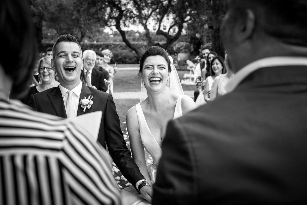 la sposa e lo sposo ridono felici durante la celebrazione del rito simbolico di matrimonio a san gimignano