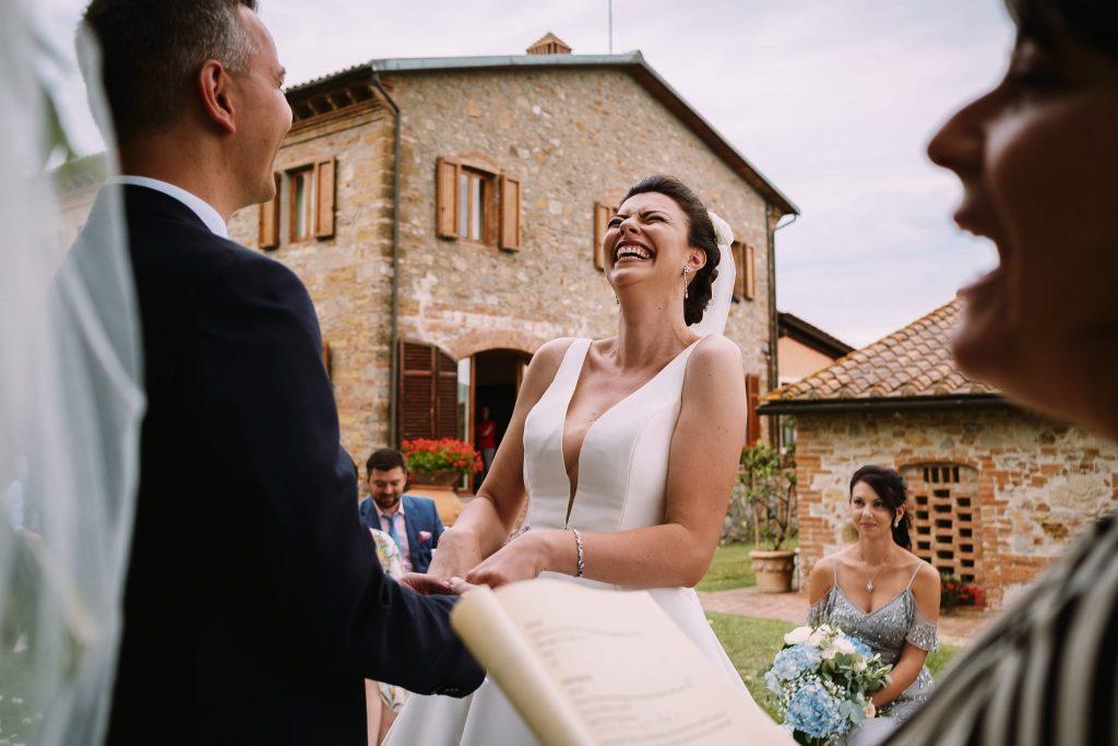 la sposa e lo sposo ridono felici durante lo scambio delle promesse al matrimonio a san gimignano
