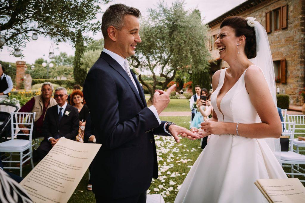 un momento divertente durante lo scambio delle fedi nuziali tra lo sposo e la sposa alla cerimonia simbolica di matrimonio a san gimignano