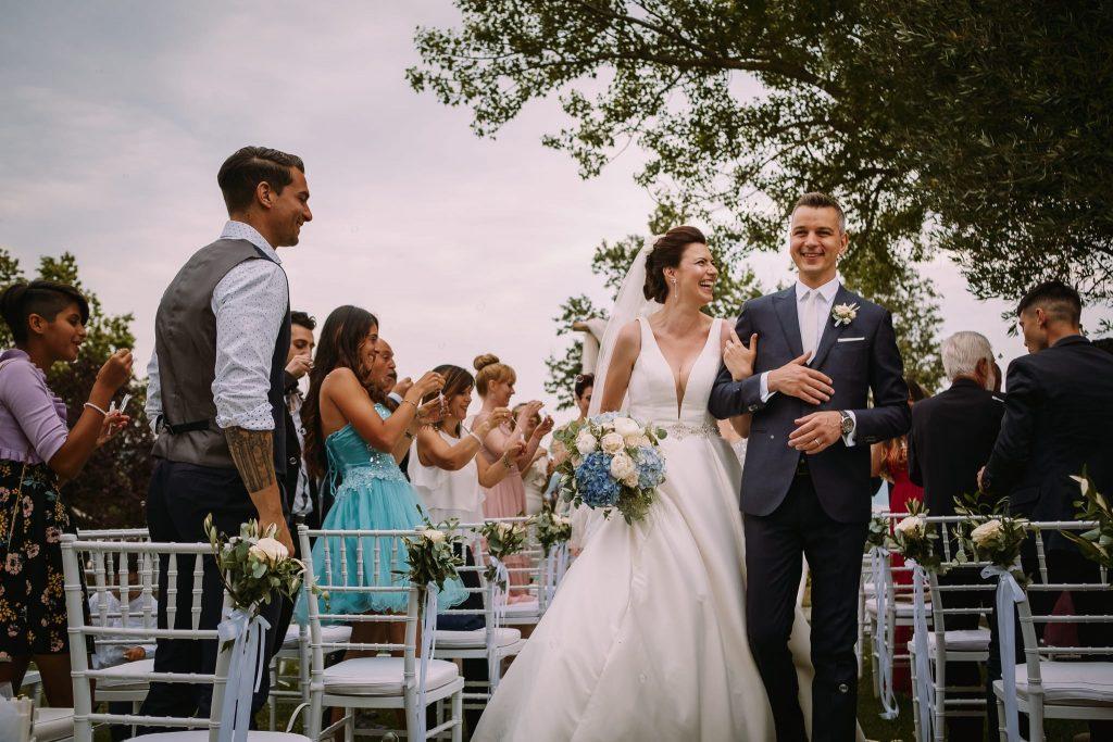 lo sposo e la sposa escono sorridenti dalla cerimonia alla tenuta quadrifoglio