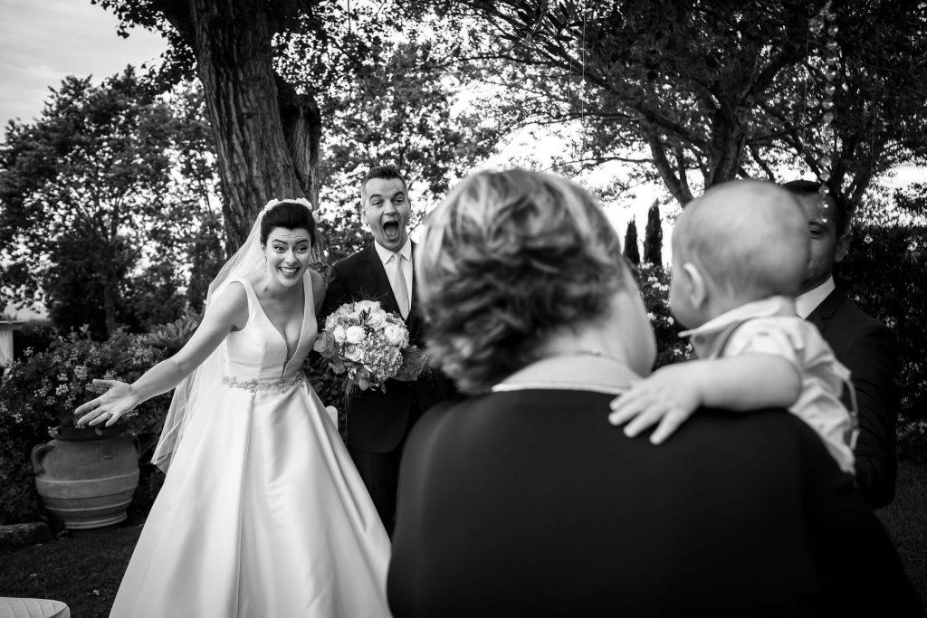 la sposa e lo sposo guardano sorpresi e divertiti il piccolo nipotino tenuto in braccio dalla mamma dello sposo