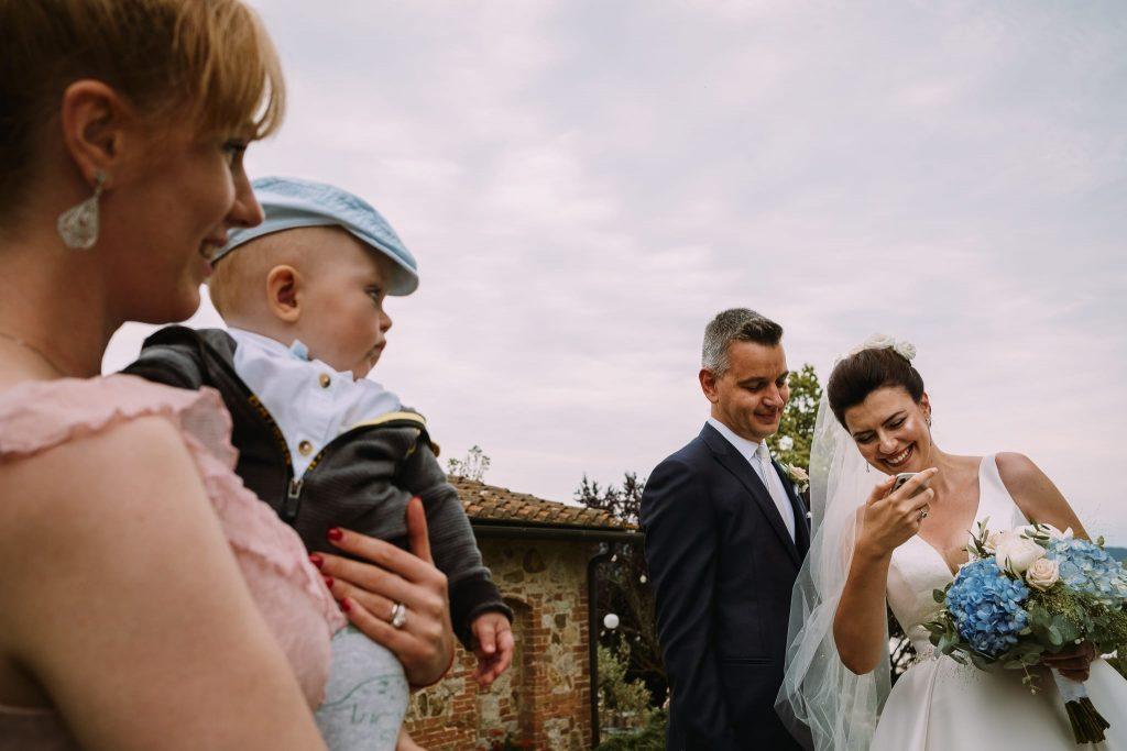 la sposa e lo sposo fanno una videochiamata al papà della sposa mentre un invitata li guarda con un bambino in braccio