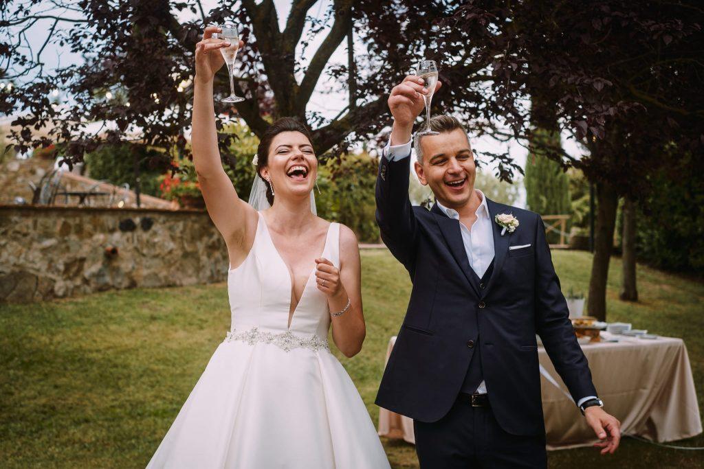 gli sposi brindano verso gli invitati e danno inizio al ricevimento di matrimonio a san gimignano