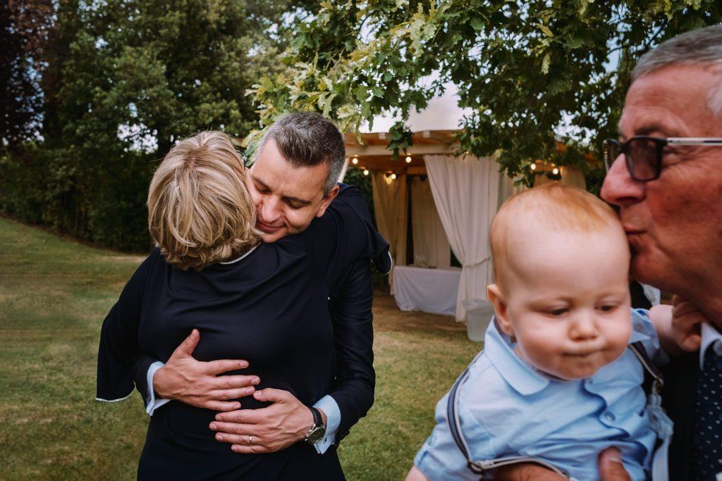 lo sposo abbraccia la mamma mentre il padre dello sposo bacia il nipotino che tiene in braccio