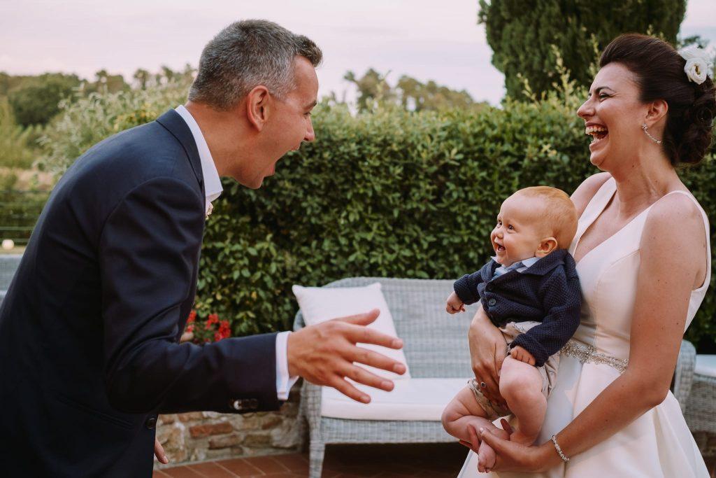 gli sposi felici ridono e scherzano con il nipotino