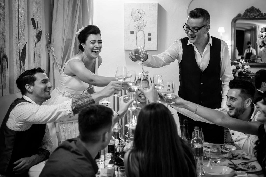 gli sposi brindano felici con gli amici durante la cena di matrimonio a san gimignano