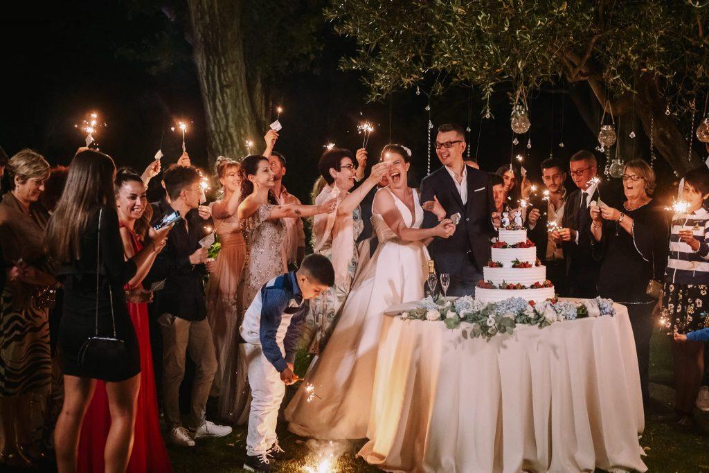 gli sposi tagliano la torta nuziale circondati da tutti gli ospiti con le stelline luminose