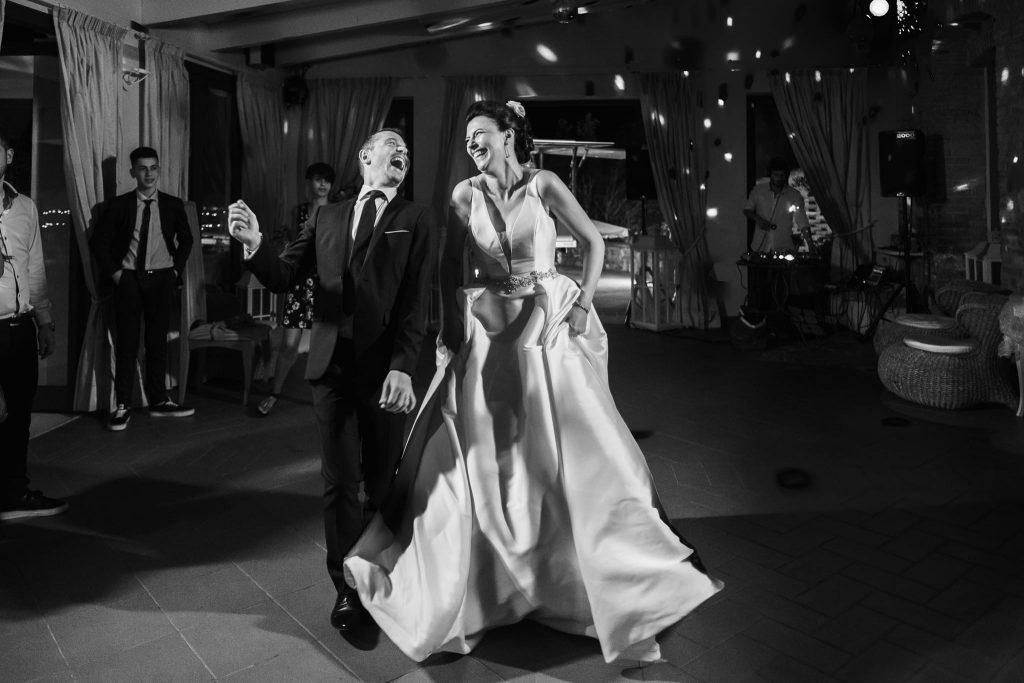 la sposa e il fratello dello sposo ballano in pista divertendosi al matrimonio a san gimignano