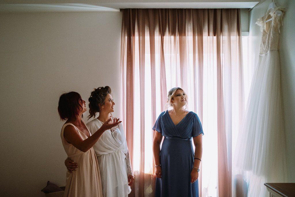 sposa-insieme-alla-mamma-ed-alla-sorella-guardano-abito-da-sposa-durante-la-preparazione-della-sposa-campioni-europei-2020