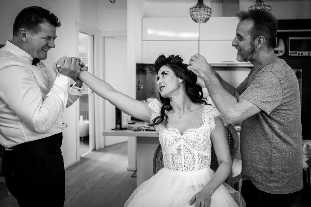 papa-della-sposa-bacia-la-mano-di-sua-figlia-mentre-il-parrucchiere-sistema-i-capelli-della-sposa