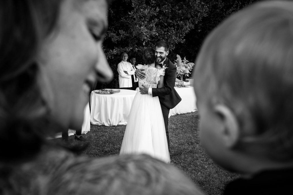 sposi-ballano-mentre-una-mamma-tiene-in-braccio-il-figlio-e-sorride-durante-ricevimento-di-matrimonio