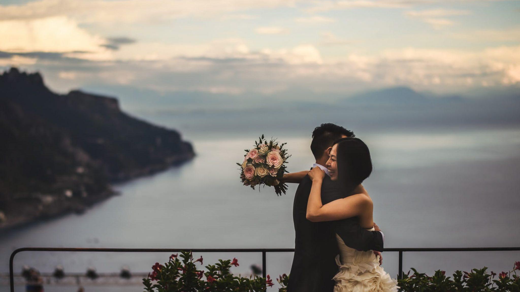 foto di coppia degli sposi che si abbracciano a villa rufolo con vista sulla costiera amalfitana