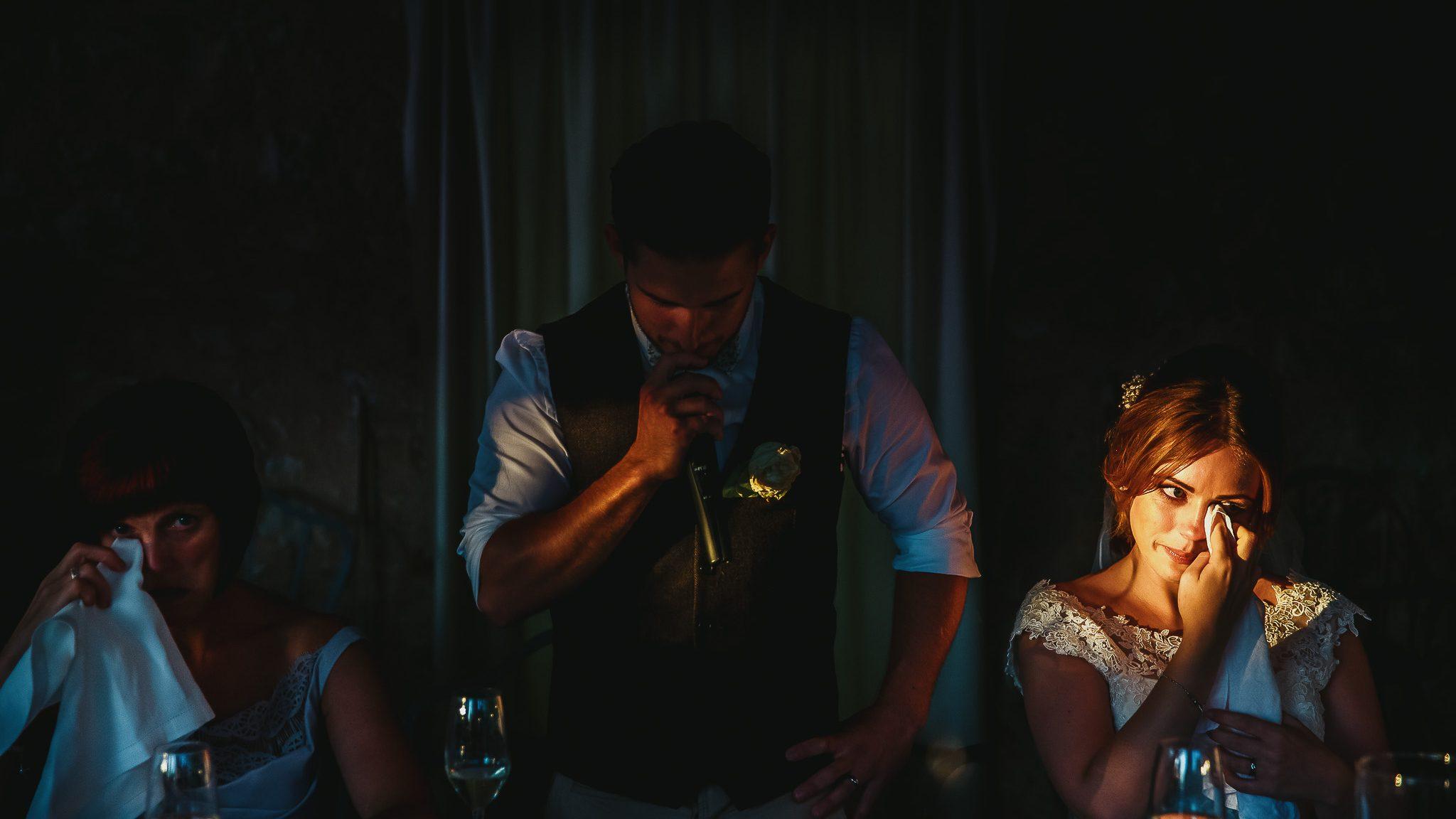 fotografare matrimoni in luce ambiente significa cogliere questo raggio di sole che illumina il viso emozionato della sposa durante il discorso dello sposo al ricevimento