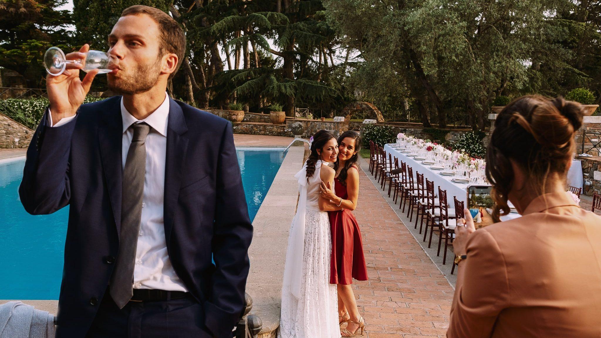 la sposa e la sorella della sposa si fanno fare una foto a bordo piscina dalla testimone mentre un altro invitato beve un prosecco in primo piano